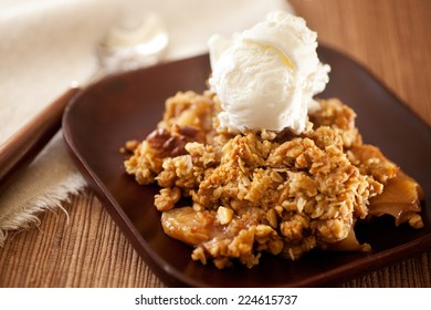 Hot dessert with vanilla ice cream. Apple Crisp made with oatmeal, sugar, walnuts and apples. Nice treat on cold winter days.