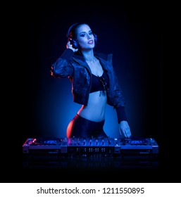 Hot DJ woman in party outfit, colorful stage lighting.