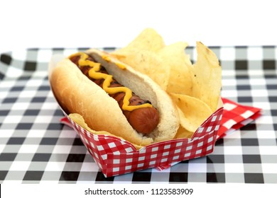 Hot Dog. Hot Dog in bun and potato chips with mustard squiggle on a black and white checker serving tray. isolated on white. room for text.