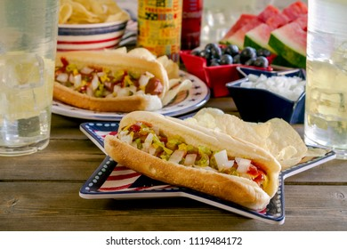 Hot dog with condiments sitting on red, white and blue star shaped plate and 4th of July themed picnic