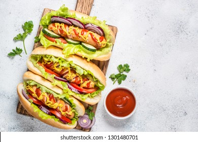 Hot dog with fresh vegetables and ketchup on white stone table. Top view with copy space.