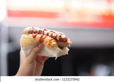 Hot dog. A hand holding half bite hot dog.