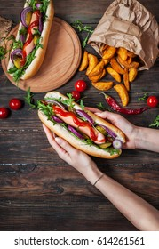 Hot dog in the hands of women on a wooden table. Top view