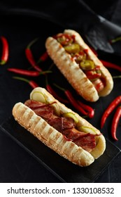 Hot dog with jalapeno and red hot chilli peppers on black  background