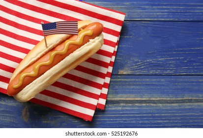 Hot dog with mustard and small USA flag on napkin
