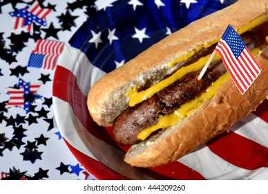 Hot dog  on an American flag plate and toothpick. Celebrating Independence day on 4th July in USA.