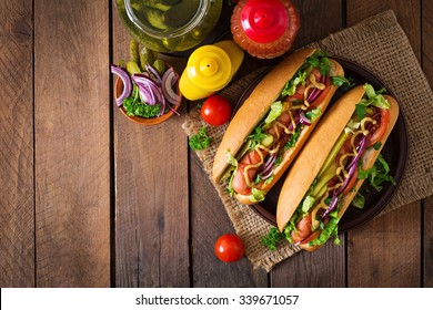 Hot dog with  pickles, tomato and lettuce on wooden background. Top view