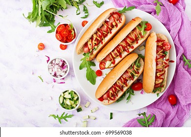 Hot dog with sausage. bacon, cucumber, tomato and red onion on white plate. Top view. Flat lay.