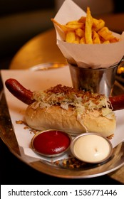 a hot dog with sausages and sauerkraut, ketchup and mayonnaise( two sauces) are on a plate, French fries in a bucket, food on a tray,  (vertically)