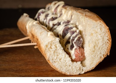 Hot dog with various toppings in wooden tray
