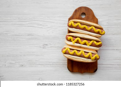 Hot dog with yellow mustard on wooden board on white wooden background, view from above. Flat lay, overhead, top view. Copy space.