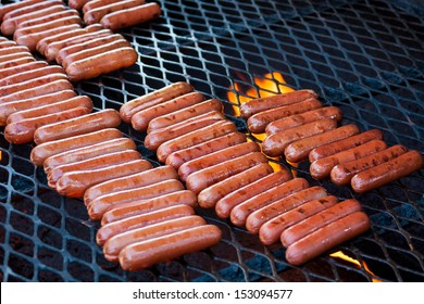 Hot Dogs cooking on a large grill