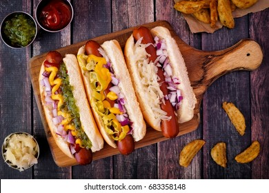 Hot dogs fully loaded with assorted toppings on a paddle board, overhead scene