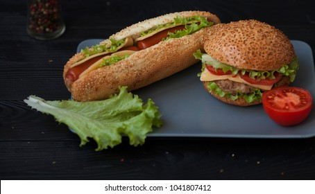 Hot dogs and hamburgers on the plate on wooden background. Street food. bistro Cafe