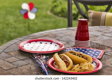 Hot dogs at a July 4th cookout are dressed with ketchup and mustard and are served with potato chips.  This image is in one in a series of patriotically themed images.