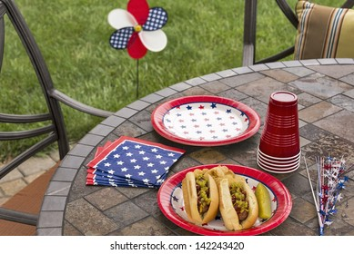 Hot dogs at a July 4th cookout are dressed with ketchup, mustard and relish and are served with potato chips and a pickle.  This image is in one in a series of patriotically themed images.