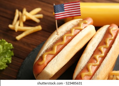 Hot dogs with mustard and small USA flag on slate plate, closeup