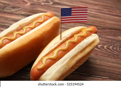 Hot dogs with mustard and small USA flag on wooden background