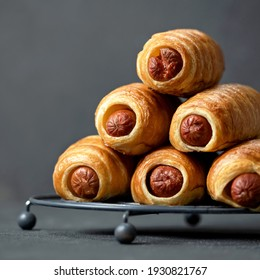 Hot dogs snack on gray background, close up. Pyramid of freshly baked sausage in puff pastry. Food concept. Copy space at left side. Square format or 1x1 for posting on social media.