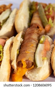 hot dogs stuffed with cheese wrapped with bacon in a bun close up