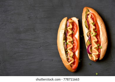 Hot dogs with tomato, marinated cucumbers, onion on dark stone background with copy space. Top view, flat lay