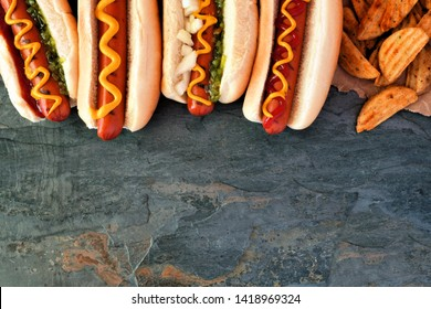 Hot dogs with toppings and potato wedges. Top border, overhead view on a dark stone background with copy space.