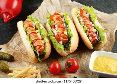 Hot dogs with vegetables and french fries on wooden table