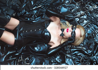 Hot dominant beautiful blonde mistress woman in shiny latex fetish corset and mask posing on bdsm accessories and fetish clothing