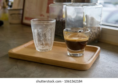 hot double espresso or ristreto coffee and sparkling water with ice in transparent cup on the wooden table near window in the cafe.