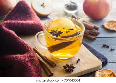 Hot drink (apple tea, punch) with cinnamon stick, star anise and clove. Seasonal mulled drink on wooden background. Hot drink with apples for autumn or winter holidays.
