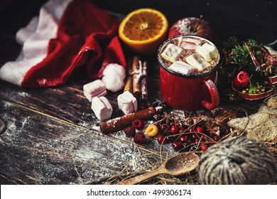Hot drink with berries and Christmas toys around on the table