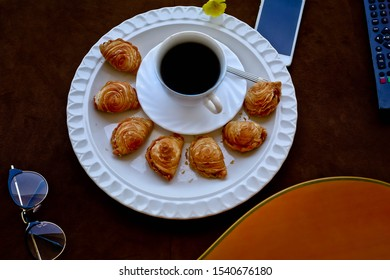 Hot drink Black coffee served with curry puff pastry on the table with a mobile phone remote control,glasses and guitar placed beside the table.