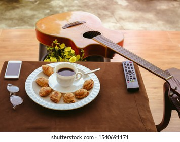 Hot drink Black coffee served with curry puff on the table with a mobile phone remote control, glasses and guitar placed beside the table.