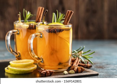Hot drink cocktail for New Year, Christmas, winter or autumn holidays.Toddy. Mulled pear cider or spiced tea or grog with lemon, pear, cinnamon, anise, cardamom, rosemary.