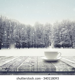 Hot drink in the cup on wooden table over winter snow covered forest. Beauty nature background
