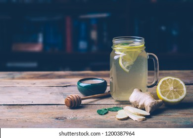 Hot drink with honey, lemon and ginger on wooden background. Concept of natural medicine. Winter or autumn drinks. Copy space