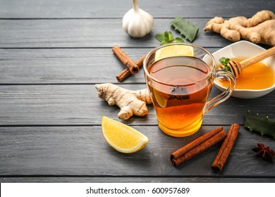Hot drink with honey, lemon and ginger for cough remedy on wooden table