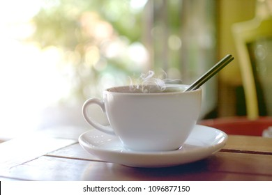 Hot drink with steaming of white cup on the wooden table with bokeh of tree background