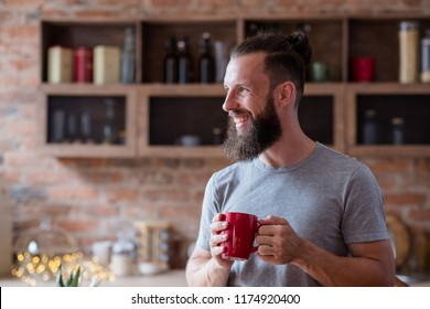 hot drinks and good or bad habits concept. happy smiling bearded man standing in the kitchen and having a cup of tea or coffee. relaxing leisure.