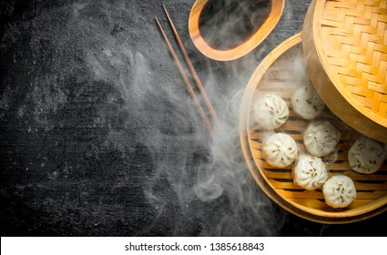 Hot dumplings manta in a bamboo steamer with soy sauce. On black rustic background