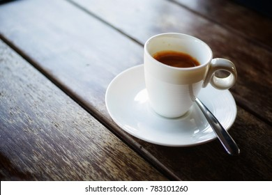 Hot espresso coffee 1 shot in small white cup on wooden table
