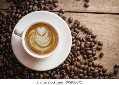 Hot Espresso Coffee cup and Coffee beans with latte art on wooden background. Top view with copy space for your text