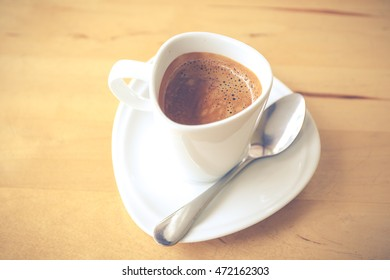 Hot espresso in white cup on wooden table close up.(Processed in vintage colour tone)