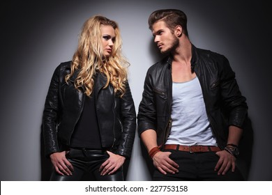 Hot fashion couple leaning on a grey wall while looking at each other, both holding their thumbs in the pockts.