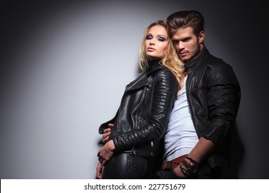 Hot fashion woman leaning on her lover while he is looking away from the camera.