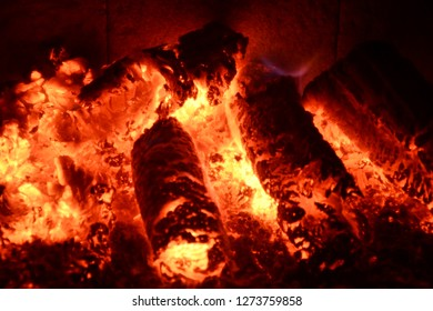 Hot Fireplace With Smouldering Wood Briquettes Glowing in Yellow and Red Colour with Contrast of Black Backround