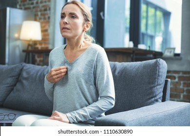 Hot flashes. Exhausted mature woman resting on sofa and having hot flash