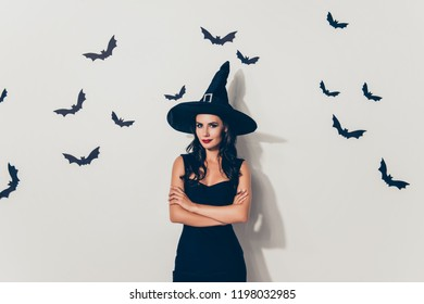 Hot flirty brunette slim lady magician, in dark dress, with crossed hands, in cap, with bright red lips, charming and elegant, stands on white wall background with black vampires on it, creepy glance