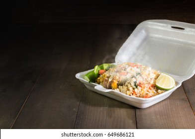Hot food in foam box on wood table and dark tone, dangerous to health