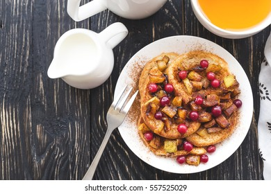 Hot french toasts with cinnamon, cranberry and caramelized apples, and tea for breakfast. Closeup